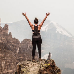 Empowered woman on top of a mountain with her arms in the air
