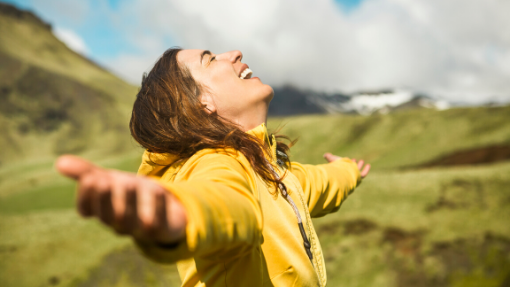 Woman in yellow coat on hillside with arms out stretched. Breathing in wellness