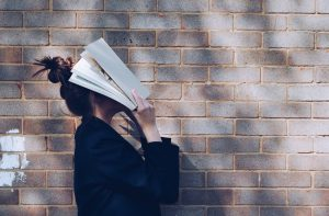 Woman in dark jacket holding book up to her face in dismay